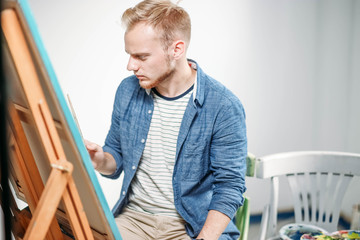 young male artist paints a picture in a creative studio on canvas with oil paints.