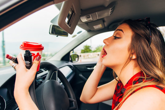 Young recklessly woman in car doing make up
