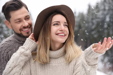 Cute couple outdoors on snowy day. Winter vacation