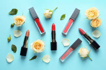 Flat lay composition with lipsticks and roses on color background