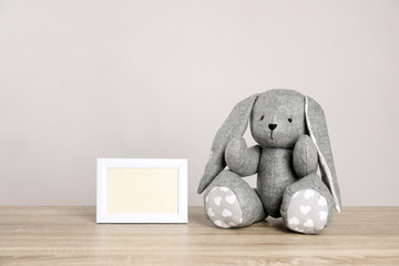 Photo frame with space for text and adorable toy bunny on table against light background. Child room elements