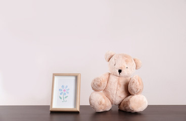 Adorable teddy bear and frame with cute picture on table against light background, space for text. Child room elements