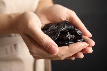 Woman holding handful of dried plums, closeup. Healthy fruit