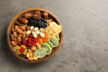 Plate with different dried fruits and nuts on table, top view. Space for text