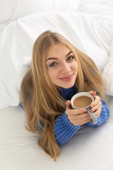 Beautiful young woman with cup lying in bed at home. Winter atmosphere