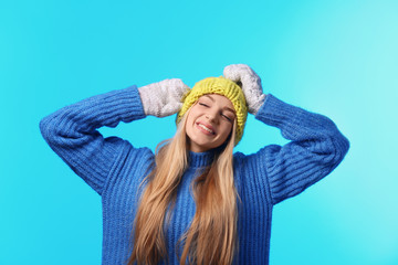 Portrait of emotional young woman in stylish hat, sweater and mittens on color background. Winter atmosphere