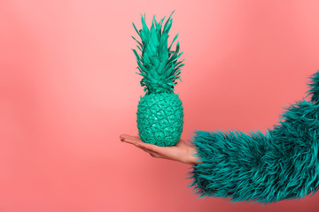 Pop art fashion girl with pineapple turquoise in the hands on a pink background. coat semi fur and...