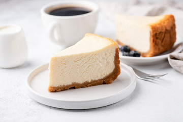 Cheesecake New York with cup of coffee on white table. Closeup view. Coffee break with slice of...