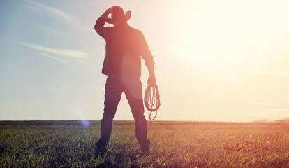 A man cowboy hat and a loso in the field. American farmer in a field wearing a jeans hat and with a loso. A man is walking across the field silhouette