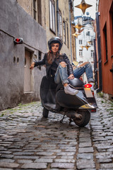 Girl wearing a leather jacket and ripped jeans sitting on a black classic scooter on the old narrow street of Europe.