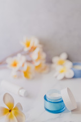 group of skincare products including moisturiser scrub and hand cream pots on marble table with exotic frangipani flowers