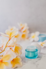group of skincare products including moisturiser and scrub pots on marble table with exotic frangipani flowers