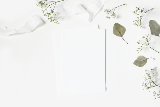 Feminine wedding styled desktop stationery mockup scene. Blank greeting card, envelope, baby's breath Gypsophila flowers, dry green eucalyptus leaves, satin ribbon on white background. Flat lay, top.