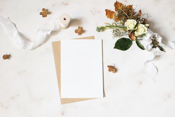 Feminine winter wedding, birthday stationery mock-up scene. Blank greeting card, envelope. Dry hydrangea, white roses and gypsophila flowers bouquet. Marble stone table background. Flat lay, top view.