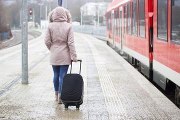 Junge Frau mit Koffer am Bahnhof