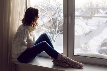 girl in a white knitted sweater sitting by the big window