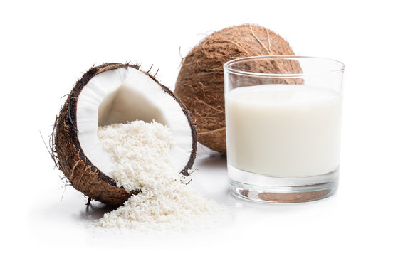 Glass of fresh coconut milk and flakes isolated on white