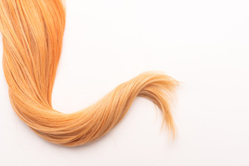 Human, natural honey-colored blond hair on white isolated background. Stylish, fashionable colors this year. Honey blonde shaken, wave and undulating hair. An example of hairstyle.