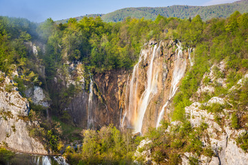 Early morning sunlight illuminates Veliki Slap waterfall and surrounding forests, Plitvice Lakes National Park, Croatia