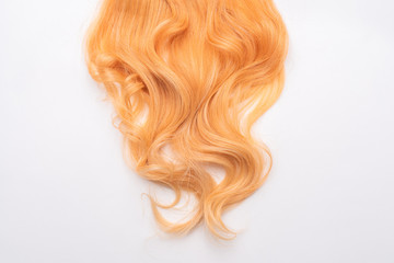 Fototapeta Human, natural honey-colored blond hair on white isolated background. Stylish, fashionable colors this year. Honey blonde shaken, wave and undulating hair. An example of hairstyle.