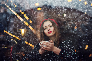 Young beautiful fashionable lady  wearing beret, polka dot blouse drinks coffee or tea in cafe. Model looking at camera. Winter holidays concept. Copy, empty space for text