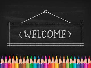 'Welcome' text drawn with chalk on black board. In bottom are color pancils.