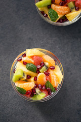 Bowl of healthy fresh fruit salad on black background.