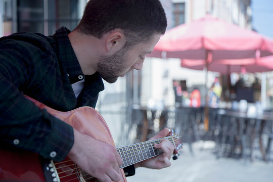 Caucasian man playing the guitar outdoors on summer day in old european city. Rest, tourism, music concept.