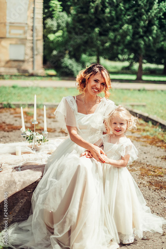 bf4aabdff2ae7 Mother bride in wedding dress and elegant daughter outdoors in ...