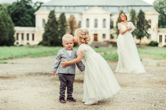 Happy mother bride in elegant fashion dress with children in park. Childhood, love, family, maternity,wedding concept