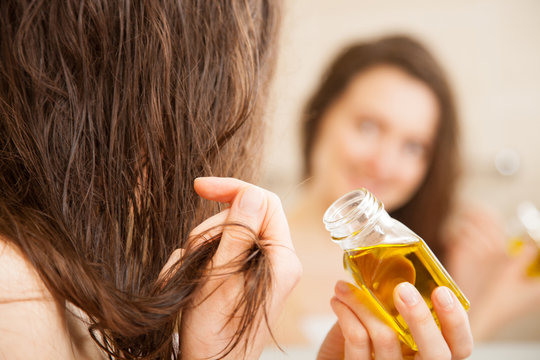 Young woman spreading oil mask over her hair