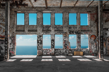 Foto auf AluDibond Graffiti Abandoned factory ruin / warehouse loft with windows and ocean and blue sky background