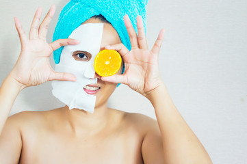 Happy woman with a clay mask with biting slice of orange. Photo of attractive young woman with towel on her head on beige background.