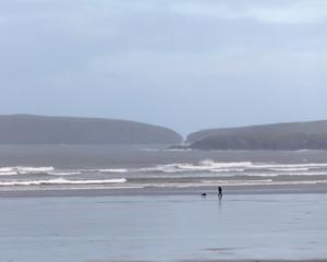 Man walking dog on beach in cold, windy winter UK