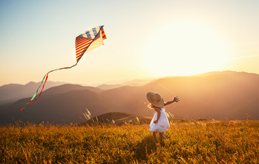 happy child girl running with kite at sunset outdoors