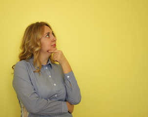 Business young blond woman in a blue shirt on a yellow background.  Copy space for text.