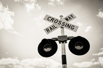 Isolated Railroad Crossing Sign with clear sky and white clouds. Railway crossing sign with flashing lights.