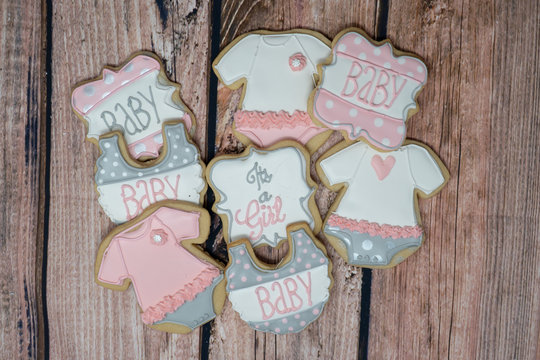 Decorated homemade Baby Shower cookies for a girl theme, decorated in royal icing in pink, gray and white colors on a wooden background