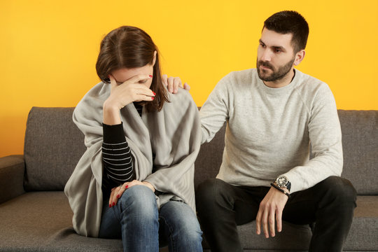 Handsome young man comforting a sad girl - couple, family or friendship relationship