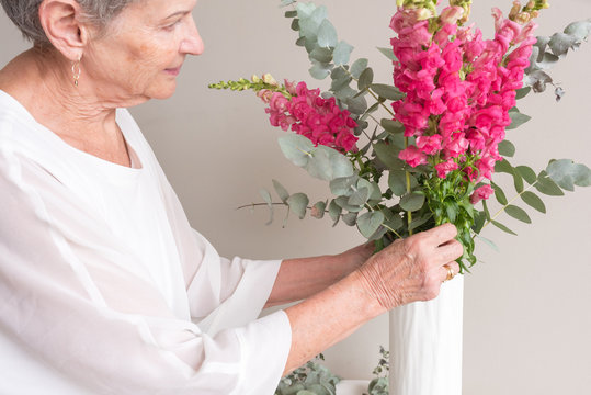 Closeup of senior woman in white top arranging pink snapdragons and eucalyptus leaves in vase against neutral wall background (selective focus)