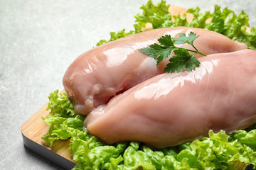 Wooden board with raw chicken breasts and lettuce on grey background