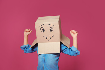 Cute little child wearing cardboard box with smiling face on color background