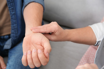 Mature woman checking man's pulse with fingers indoors, closeup