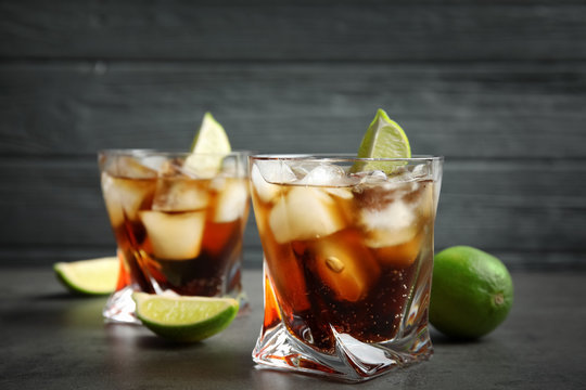 Glasses of cocktail with cola, ice and cut lime on table