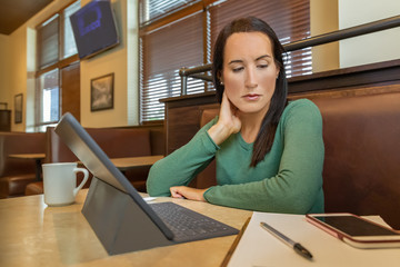 A young female works out of the office gets distracted by her cell phone while sitting in front of the tablet in a booth. She sits alone at the cafe focused on her work at a table and phone beeps.