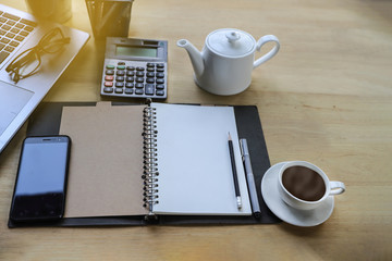 workspace business with note book, pen smartphone,laptop computer, cup of coffee and calculator on woode table background - image