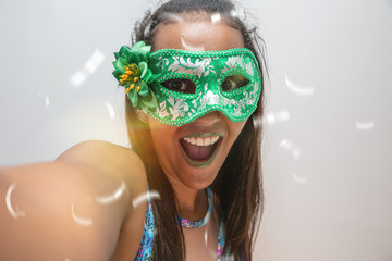 people, holidays, emotion and carnival concept - happy young woman with mask and confetti at carnaval party. Carnaval concept