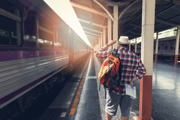 Asian traveler man with belongings waiting for travel by train