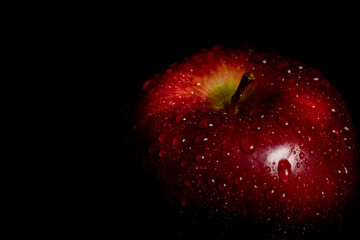 top view of apple with water drops on black background