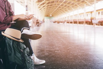 portrait the tourist young man traveler with backpack sit waiting train station and public car look at the he hand use the phone to check the schedule to leave travel at the station.Travel concept. Wall mural